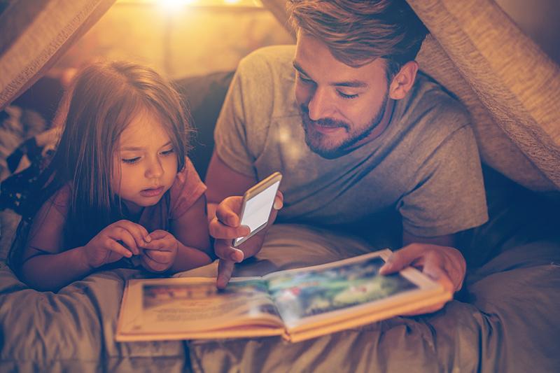 Pappa och dotter läser bok i koja.