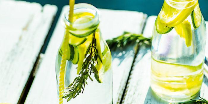 Två flaskor kranvatten med citron- och limeskivor står på en brygga.